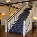 Photo of a commercial stair with custom newels posts, wood balusters, and ADA compliant railing. The custom newels are carved in the shape of lighthouses.