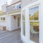 Exterior photo of a coastal home with a deck. Deck features cable railing.