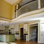 Photo of a grand room with a kitchen and balcony above. Balcony is curved with wood balusters and box newels.
