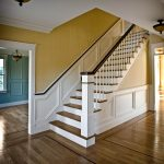 Photo of a straight stair with box newels and wood balusters. Stair features paneled wainscoting.
