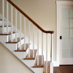 Straight stair with a turned newel post and wood balusters.