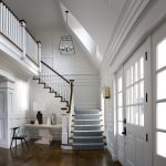 Straight L-shaped stair with box newels and wood balusters in a grand foyer. Stair features a large balcony.