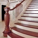 Photo of a grand staircase with a large intricately custom carved newel post. Stair flairs at its base and features mahogany treads and railing.