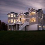 Twilight photo of a coastal home with a large deck. The deck features glass railing.