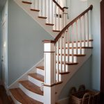 Photo of a straight scissor stair with box newels and wood balusters. Stair features reclaimed wood treads and sepele mahogany railing. Stair has a slight flair at its base.