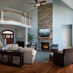 Photo of a great room with a grand balcony. Balcony features wood square balusters and box newels.