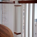 Photo taken from a balcony in a residential home showing square wood balusters, a box newel, and curved railing..