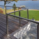 Photo of an exterior balcony overlooking the ocean. The balcony features modern cable railing.