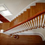 Photo taken from above of a curved stair with box newels and wood balusters.