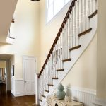 Photo of a curved stair with box newels and wood balusters. The stair features beadboard wainscoting.