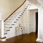 Curved stair with box newels and wood balusters. The stair features beadboard wainscoting and curves sharply at its top.