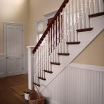 Photo of a straight stair with box newels and wood balusters. The stair features beadboard wainscoting.