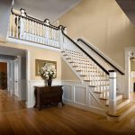 Photo of a straight stair with box newels and wood balusters in a grand foyer. Stair features a large balcony.