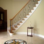 Curved staircase with wrought iron balusters and over-the-post railing.