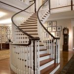 Curved unsupported staircase with wood balusters in a grand foyer.
