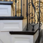 Photo of curved stair with wrought iron balusters. Custom detail has been applied to the risers. Stair features unique paneled risers.