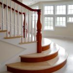 Photo of a straight stair with custom legacy newel posts and unique round starting steps.