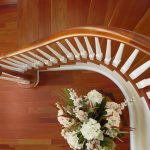 Photo taken from above of a curved stair with wood balusters.