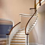 Curved stair with wood balusters and over-the-post railing.