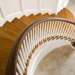 Photo taken from above of a curved staircase with paneled wainscoting, wood balusters, and over-the-post railing.