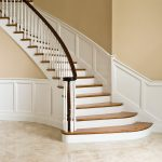 Photo of a curved staircase with paneled wainscoting, wood balusters, and over-the-post railing.