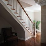Photo of a straight stair with wood balusters and over-the-post railing.