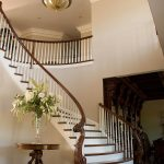Photo of a curved staircase with a custom carved wood newel post and wood balusters.