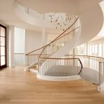 Photo of a grand multi-level stacked unsupported curved staircase with steel balusters in a modern home.