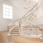 Grand multi-level stacked unsupported curved staircase with steel balusters in a modern home.