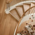 Photo taken from above of a grand multi-level stacked unsupported curved staircase with steel balusters in a modern home.