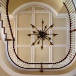 Photo taken from below of a grand curved balcony with wood balusters.