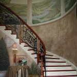 Curved stair with custom wrought iron balusters.