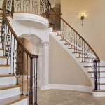 Double curved stair with wrought iron balusters in a grand foyer.