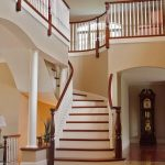 Photo of a curved staircase with custom turned newel posts and wood balusters in a grand foyer.