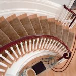 Photo taken from above of a curved staircase with wood balusters.
