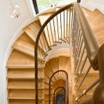 Photo taken from above of a multi-level stacked staircase with modern steel balusters and over-the-post railing.