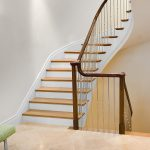 Multi-level stacked staircase with modern steel balusters and over-the-post railing.