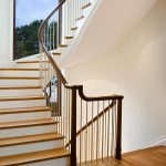 Photo of a multi-level stacked staircase with modern steel balusters and over-the-post railing.
