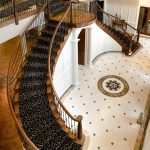 Double curved stair with wrought iron balusters in a luxury home.