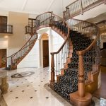 Photo of a double curved stair with wrought iron balusters in a luxury home.