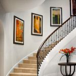 Photo of curved stair with wrought iron balusters and stone treads and risers.