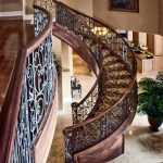Unsupported curved stair with custom wrought iron balusters.