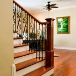 Straight stair with a box newels and wrought iron balusters.