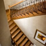 Photo taken from above of a straight scissor stair with wrought iron balusters.