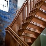 Straight unsupported scissor stair with open risers and a custom balustrade in a modern home.