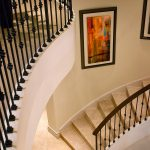 Curved stair with wrought iron balusters and stone treads and risers.