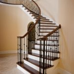 Photo of curved stair with wrought iron balusters.