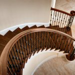 Photo taken from above of curved stair with wrought iron balusters.