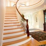 Flared stair with a custom legacy newel post an wood balusters.