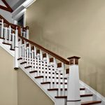 Photo of a unique straight stair with custom balusters and a custom newel post.